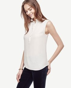 "Topped with a pretty ruffle collar, this sleeveless style is weekday-to-weekend perfect. Ruffle stand collar. Sleeveless. Hidden button front placket. Shirred front and back neckline. Front and back shoulder yoke. Shirttail hem. 26 3/4"" long."