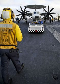 PACIFIC OCEAN (Nov. 3, 2012) Aviation boatswain's mates (handling) on board the aircraft carrier USS Nimitz (CVN 68) move an E-2C Hawkeye assigned to the Wallbangers of Airborne Early Warning Squadron (VAW) 117 prior to the evenings foreign object damage (FOD) walk down. Nimitz is currently underway participating in the ship's Composite Training Unit Exercise. (U.S. Navy photo by Mass Communication Specialist 3rd Class Ryan J. Mayes/Released) Us Navy Aircraft, Navy Aircraft Carrier, Military Aircraft, Navy Day, Go Navy, Helicopter Cockpit, Uss Nimitz, Navy Military, Flight Deck