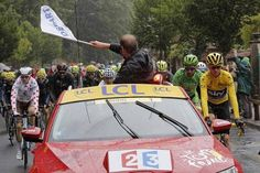 """Tour de France director Christian Prudhomme waves the """"Depart"""" flag as Britain's Chris Froome, right, and Peter Sagan of Slovakia, second right, ride Sunday in the race's final stage."""