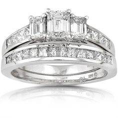 The lights may go out, but your hand will light the way if you own this dazzling bridal ring set. This sparkler features three emerald-cut diamonds set perfectly atop a brilliant, white-gold band adorned with channel-set, princess-cut diamonds.