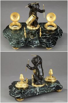 "Late 19th century gilt and patinated bronze inkwell decorated with a putto playing the drum, on a small circular base. He is flanked by two ink pots, intricately chiseled with foliages and crowned with a pine cone finial. It is set on a green ""Vert de Mer"" marble base and four toupie feet. Napoleon III period."