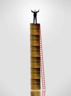 Free Photo of Businessman on top of gold coin stack - Wealth growth concept
