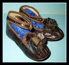 Darling pair of early 1900s pair of low cut child's shoes with ankle strap in a brown leather. Shoe button closure. Leather bow across the front of shoes. These cute shoes have been worn, however, sti