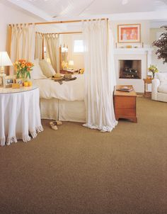 Canopy bed with white curtains and beige carpet.