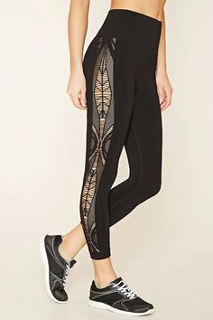 A pair of athletic leggings featuring a lasercut design at each side, moisture management, and a ribbed high waist.