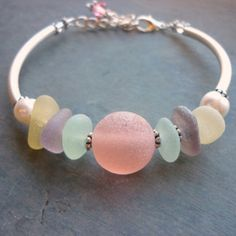 "Sea glass bracelet. So pretty. I have read that you can make ""your own"" sea glass with translucent polymer clay and tiny amounts of colored clay, but I can't believe you would get the transparency of sea glass. maybe resin would work better."
