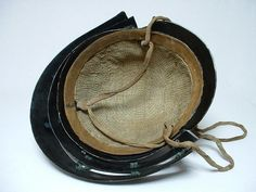Edo 18th c. black lacquered 6 plate Samurai Suji Kabuto helmet with a three lame Shikoro and Maedate, original cotton liner Ukebari and helmet cords Shinobi-no-o, brass Tehen-no-kanamono, three lame Hineno Shikoro laced with green silk cords, two blue replacement sections, Oharadaite or crest holder is the earlier two pronged construction. Fukigaeshi or side flanges and Maedate or crest is of gilded wood and plaster construction with brass rear section.