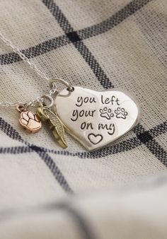 "Tell the world about the furever friend who has left an indelible print upon your heart with this charming necklace. A sweet, heart-shaped charm is adorned by a gold-tone angel wing and a copper paw print charm, with the message, ""You left your paw prints on my ♥."""