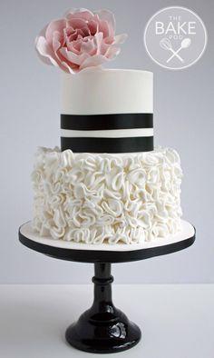 Two tier black and white wedding cake with ruffles and a pink sugar rose. #sugarrose #weddingcake #rufflecake #blackandwhitecake