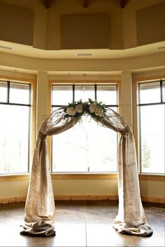 decorate a plain florist arch (usually you can rent them for around $30) with burlap draped from the top center tied at the sides where the top of the arch connects to the sides and attach four big silk flowers to the top!
