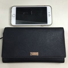Black Kate Spade wallet Large Kate spade wallet in good condition! Size compared to iPhone 6plus in photo (not included). Can fit a 6plus size phone. Holds 1 pen, 2 zippered sections, 6 card pockets, 7 other pockets, 1 ID pocket. Only wear shown on logo plate in front. kate spade Bags Wallets