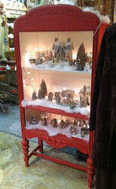 Christmas village scene in a shelf painted white inside and red outside.