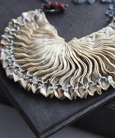 The reminder, techniques de pliages, teintures végétales aux baies de sureau ou pelure d'oignon, et smocks pourpli ces delicats bijoux textiles.