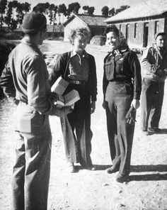 """Tex"" (left) and another flight nurse stationed with the 803rd Air Evacuation Squadron pause to speak to a soldier carrying supplies in India in 1943 or 1944. The nurse carrying gloves is wearing the blue wool Army Nurse Corps flight nurse uniform ~"