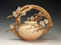 Ship Date: 2-4 weeks Wheel thrown whiteware non-functional teapot with sculpted branch handle with hand formed and attached plum blossoms. Underglazed with Soft coral blush and clear finish. Other col