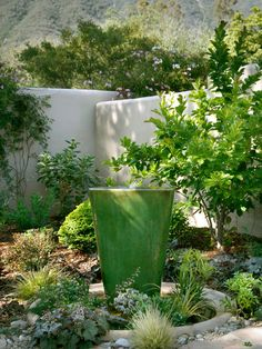 A bubbling green water fountain creates a soothing ambiance in this courtyard garden.