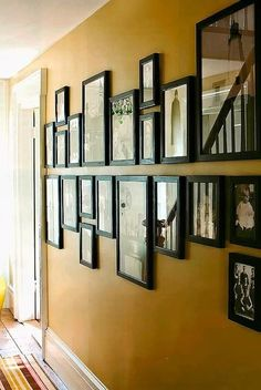 Draw a line along the wall, line frames up below and above it. Love this, great for a hallway!