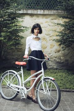 Vintage French glamour.   Classic bicycle, pleated skirt, loafers and a white shirt with heart cut out.