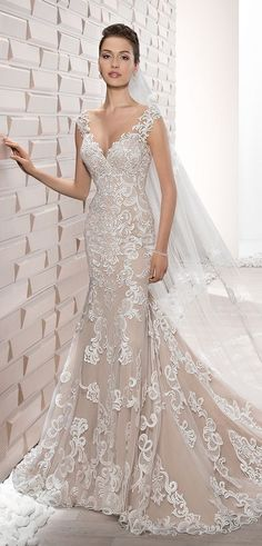 Intricate lace embroidery coupled with a dramatic illusion back and buttons create this glamorous fit n flare gown. Delicate lace on the shoulders flowing into a Sweetheart neckline over barely there Illusion and a Chapel train add the perfect touches.