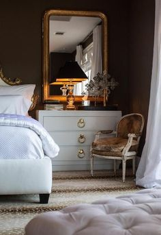 Chic French bedroom features a baroque bed next to a white lacquered nightstand accented with gold ring pulls topped with a crystal baluster lamp with black shade placed in front of a gold leaf arched mirror alongside a brown cowhide French chair atop an antelope rug.
