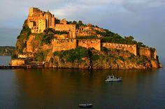 Small rocky island with 15th century Aragonese Castle at sunset. Castello Aragonese, Ischia ponte, Ischia island, Campania, Bay of Naples, Italy