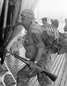 George Esper captures a US Marine with rifle, American flag on his pack and an inscription 'Goodbye Vietnam' on his helmet, boards an Okinawa-bound transport plane at Quang Tri, South Vietnam, July 10, 1969.