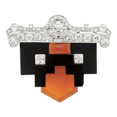 Art Deco Platinum, Black Onyx, Carnelian and Diamond Clip-Brooch Topped by a pierced plaque of scroll design accented by 13 old European-cut diamonds approximately 2.90 cts., supporting fancy-shaped overlapping black onyx and carnelian panels of geometric motif, accented by two diamond-set square-shaped plaques, set throughout with 27 single-cut diamonds approximately .95 ct., circa 1930, approximately 18.8 dwts.
