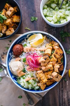 Spicy Tofu Rice Bowl. A basmati cilantro rice bowl, topped with harissa, hummus, diced cucumber and tomato, pickled onion, spicy harissa dressing and harissa marinated tofu.