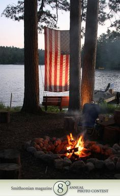 American flag, hanging between two trees by a lake.