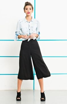 10 Maneiras de misturar jeans e alfaiataria num visual mega cool. Camisa jeans com nozinho na cintura, calça pantacourt preta, sapato preto