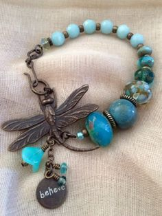 A majestic brass Queen Dragonfly from Vintaj Natural Brass and her body full of amazing color made up of Czech glass beads in shades of blue, a handmade lampwork glass bead from Havana Beads, a handma