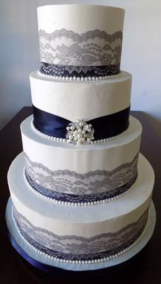 4 Tier buttercream wedding cake, decorated with navy blue ribbons, grey/silver lace, fondant pearl borders and a pearl and diamond brooch. Flavor of cake was red velvet cake, filled with cream cheese icing, iced in vanilla buttercream and delivered to the Heritage Hills Gold Resort York PA