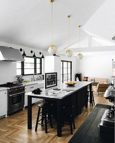 A row of gold bistro-style pendant lights stands out in a monochromatic black and white tuxedo kitchen.