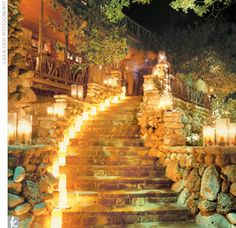 Pillar candles lined the curved stairway outside the stone lodge, and luminarias lit the paths around the tent where the reception took place, creating a warm ambience. A mix of seasonal blooms in faux bois containers sat atop the tables.