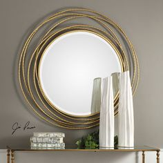 Interlinked rings in a metallic gold leaf finish give the Uttermost Whirlwind Gold Round Mirror its contemporary glamour. Its round mirror within the. Round Wall Mirror, Framed Mirror Wall, Round Gold Mirror, Mirror Design Wall, Mirror Interior, Mirror Wall Bedroom, Metallic Gold Leaf, Contemporary Wall Mirrors