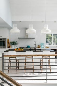 The light and bright kitchen at HGTV Dream Home 2018 with white Shaker cabinets and handsome wood-topped island has a clean and contemporary style with a user-friendly open layout.