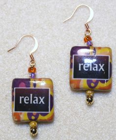 "Handcrafted by Teal Palmetto, LLC. Square, decoupaged focal beads in shades of purple, orange, pink, and yellow tell you to ""Relax"", something we all need to do more often!  The focal beads are complemented by orange, yellow, and purple glass seed beads, as well as gold-tone metal beads.  The pair has gold-tone fish hook ear wires. Price: $12"