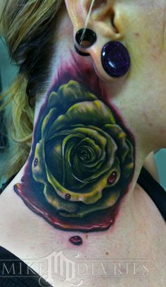 Green rose tattoo on neck