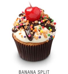 Fresh banana cupcake with a fudge core topped with a vanilla cream cheese frosting, a fudge drizzle, hazelnuts, rainbow bobbles,  and a maraschino cherry (no recipe)