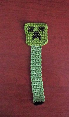 """Crochet """"Creeper"""" Bookmark (Minecraft)  12 sc across for head; enough rows to make square 3 sl st to narrow from head to body 6 sc across for body; enough rows for desired length - final row black for feet black thread for facial details - X-stitch"""