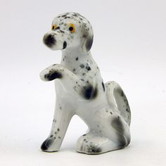 SOLD - Vintage pre-owned decorative gloss glazed porcelain ceramic collectible dog figurine. I believe this is a Dalmatian or a similar breed of dog that is sitting with one paw up to shake hands and a curled tail. Dog Sculpture, Shake Hands, Porcelain Ceramics, Dalmatian, Clay, Statue, Dogs, Vintage, Decor