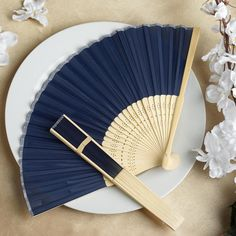 Asian Silk Folding Fans - Navy Blue | eFavorMart / Add a classical Asian touch to your wedding, or a special event by presenting your esteemed guests with this special souvenir. Our stylish silk wedding hand fan is intricately handcrafted with a bamboo structure. The framing and spines are crafted from hand-picked bamboo and durably glued with a seamless cut piece of silk to fashion this immaculate magnum opus. Give these swish fans to your respected guests and let them create the lasting…