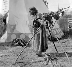 One of his black and white photographs showed a woman smoking meat on a high wooden structure by one of the traditional dwellings