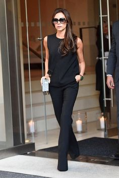 Victoria Beckham in a black tank top + black trousers + heels