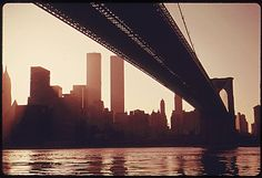 The World Trade Center seen beyond the Brooklyn Bridge Across the East River    In remembrance of September 11, 2001, a photo of the World Trade Center one year after it opened. April, 1974.
