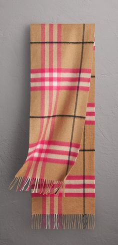 A Burberry cashmere scarf patterned with a large-scale check containing neon highlights. The fabric has been woven on traditional looms at a 200-year-old Scottish mill and washed in local spring water for a super-soft finish.