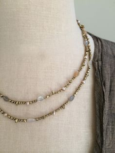 """Lis is a strand of mixed brass beads accented with faceted oval moonstones and old tibetan pearls crocheted onto blonde gore-tex thread. Fastened with an abalone button clasp this beautiful strand comes in 3 sizes. The 6x can be worn as a 39"""" long necklace, wrapped twice around the neck as a double choker or 6 times around the wrist as a wrap bracelet. The 4x measures 26"""" and the 3x measures 20"""". A beautiful stand alone piece, Lis is also a great for layering."""