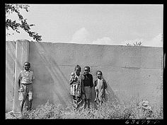 Life in gardens/enclos*ure: Black children standing in front of half-mile concrete wall  in N.W. Detroit. It was built in 1941 to separate their neighborhood from a white housing development going up on the other side. Photo taken August 1941 by John Vachon for U.S. Farm Security Administration via Library of Congress.