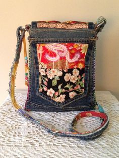 A One of a Kind Bohemian Style Handbag. I used some of my favorite fabrics and put this beautiful little bag together. I used old denim for the base and added Asian metallic fabric and some glorious batiks to make this unique bag. The bag is 7 wide and 9 1/2 inches long. Its interior
