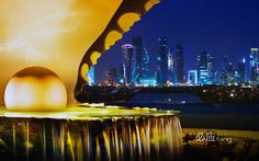 The pearl monument in the Corniche neighborhood of Doha, Qatar, illuminated at night with the new high-rises of West Bay in the background (© Jon ...